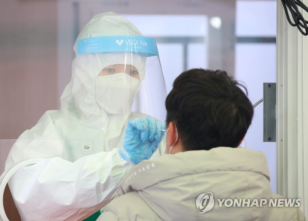 A man gets tested for COVID-19 at a screening center outside Seoul Station on March 2, 2021. (Yonhap)