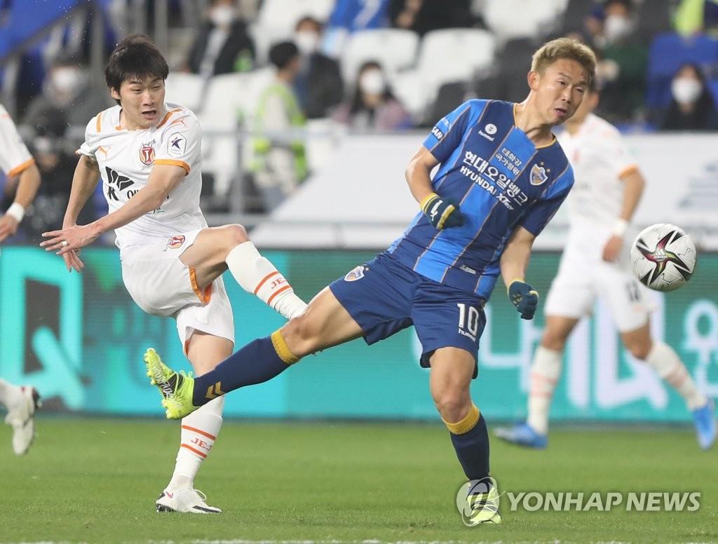 In this file photo from March 16, 2021, Kang Yoon-seong of Jeju United (L) takes a shot past Yoon Bitgaram of Ulsan Hyundai FC during a K League 1 match at Ulsan Munsu Football Stadium in Ulsan, 415 kilometers southeast of Seoul. (Yonhap)