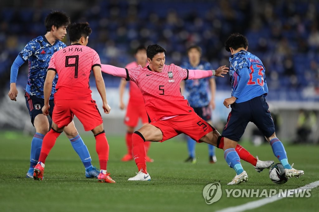 Jung Woo-young of South Korea (2nd from R) tries to steal the ball from Miki Yamane of Japan (R) during their friendly football match at Nissan Stadium in Yokohama, Japan, on March 25, 2021, in this photo provided by the Korea Football Association. (PHOTO NOT FOR SALE) (Yonhap)