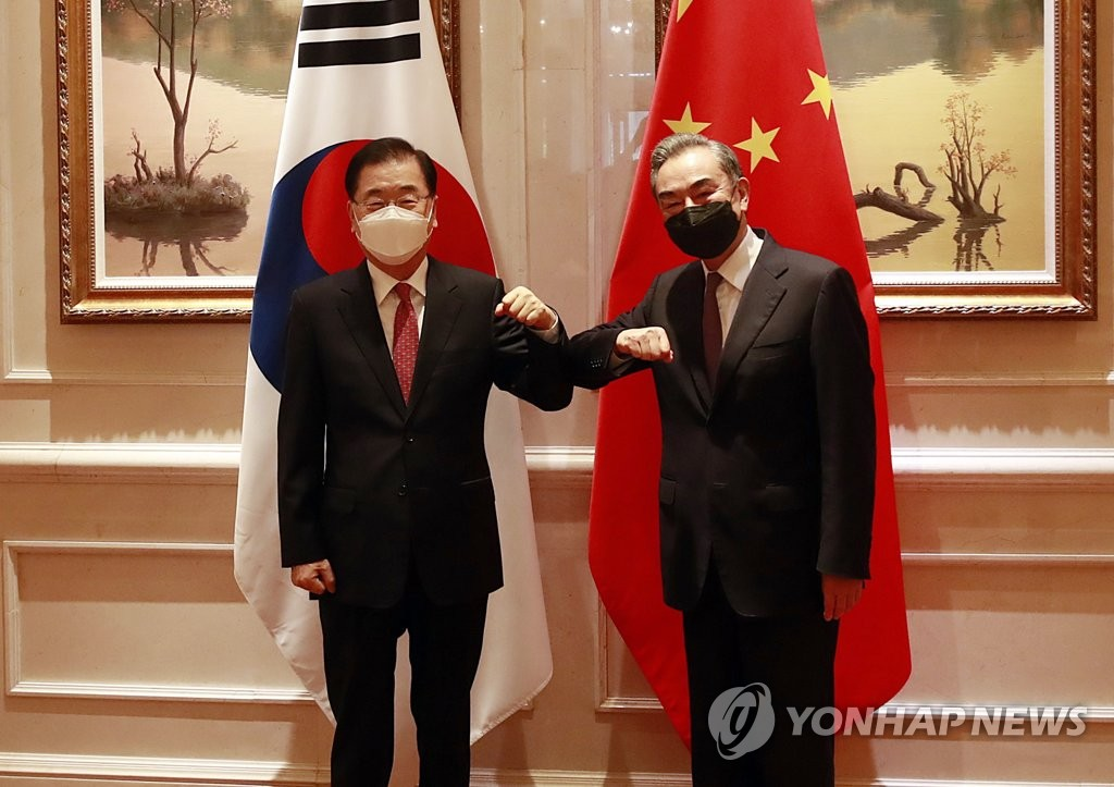 Foreign Minister Chung Eui-yong (L) and his Chinese counterpart, Wang Yi, bump elbows before their talks at a hotel in the southeastern Chinese city of Xiamen on April 3, 2021. (Yonhap)