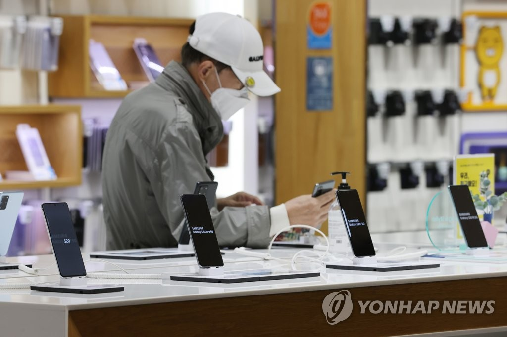 In this file photo taken on April 7, 2021, a consumer looks at smartphones from Samsung Electronics Co. at a store in Seoul. (Yonhap)