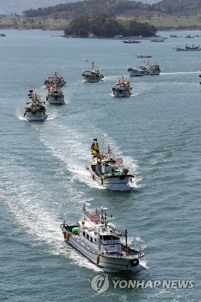 Fishing boats parade in waters off Yeosu on South Korea's south coast on April 19, 2021, to criticize Japan for its decision to discharge contaminated water from the Fukushima nuclear power plant. (Yonhap)