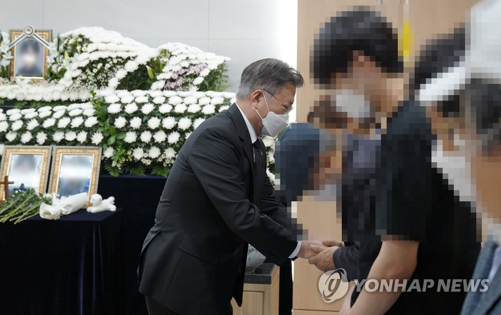 President Moon Jae-in (L) meets with the bereaved family of a late female Air Force noncommissioned officer at a funeral home of the Armed Forces Capital Hospital in Seongnam, Gyeonggi Province, on June 6, 2021, in this photo provided by Cheong Wa Dae. (PHOTO NOT FOR SALE) (Yonhap)