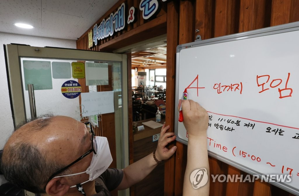 A worker fixes a notice in a restaurant in Seoul on June 30, 2021, in line with the city government's announcement that it is keeping a four-person cap on private gatherings instead of raising the limit to six. (Yonhap)