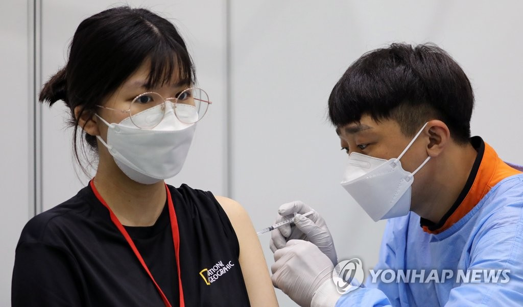 A medical worker gives a Pfizer vaccine shot to a high school senior at a vaccination center in Sejong, about 150 kilometers south of Seoul, on July 19, 2021. (Yonhap)
