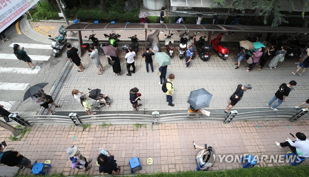 Citizens wait for COVID-19 testing at a screening station in southern Seoul on July 19, 2021. (Yonhap)