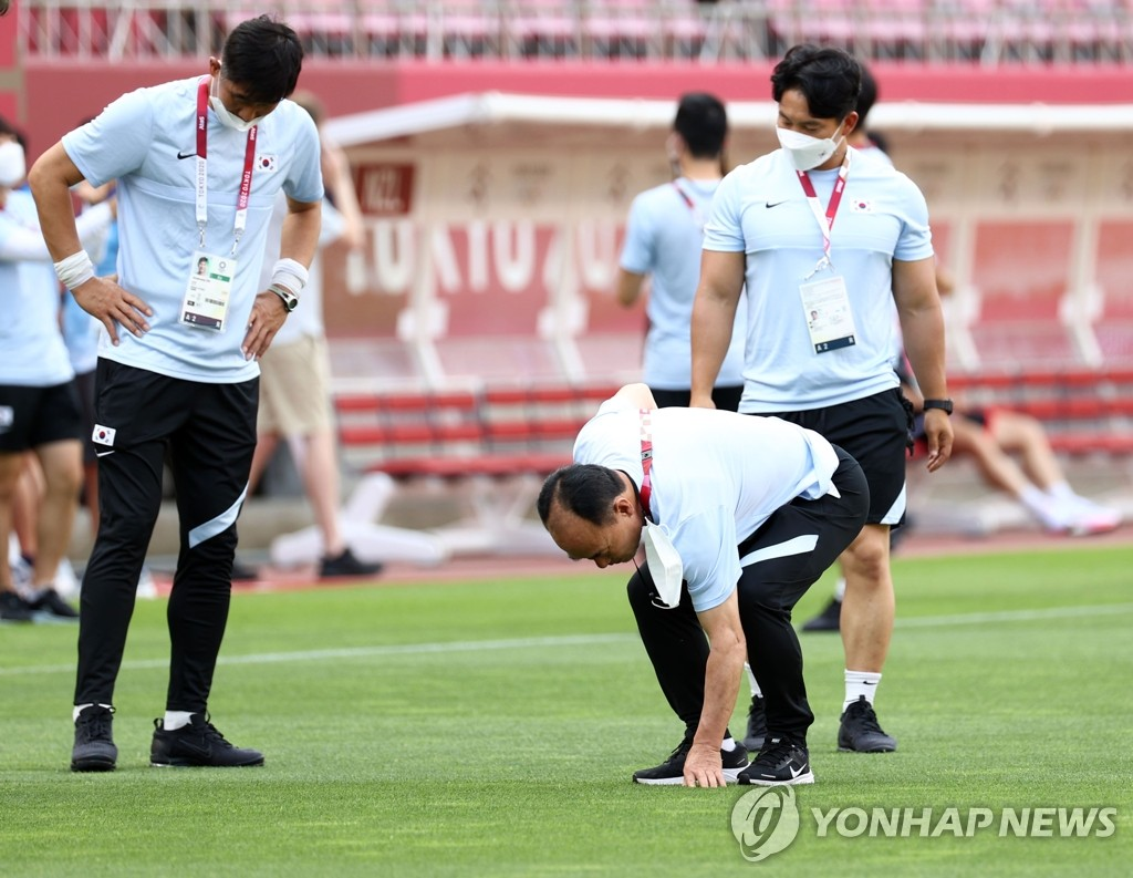 Kim Hak-bum (C), head coach of the South Korean men's Olympic football team, checks the field at Ibaraki Kashima Stadium in Kashima, Japan, on July 21, 2022, on the eve of South Korea's first match against New Zealand at the Tokyo Olympics. (Yonhap)