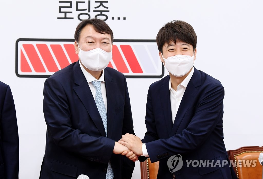 Former Prosecutor General Yoon Seok-youl (L) and the main opposition People Power Party chief Lee Jun-seok pose for photos during their meeting at the National Assembly in southwestern Seoul on Aug. 2, 2021. (Yonhap)