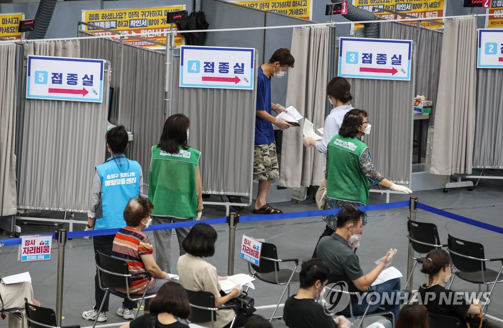 People wait to get vaccinated at a vaccine site in Seoul on Aug. 27, 2021. (Yonhap)