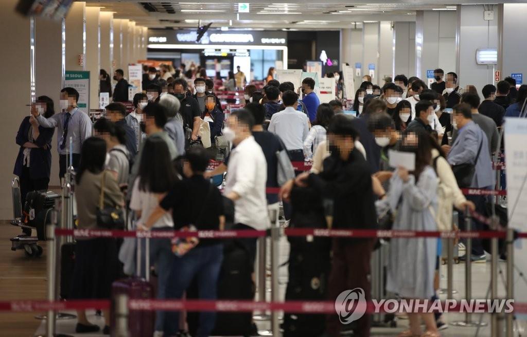 This photo taken on Oct. 8, 2021, shows people waiting at ticketing counters at Gimpo International Airport in western Seoul ahead of an extended weekend that includes Hangeul day. (Yonhap)